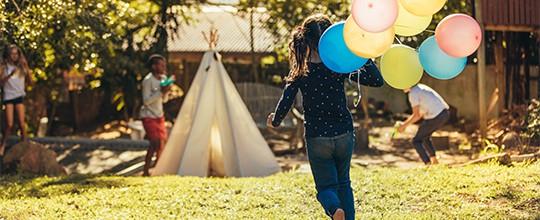 Kind rennt mit einem Bund Ballonen durch die Wiese auf ein Kinder-Tipi zu.